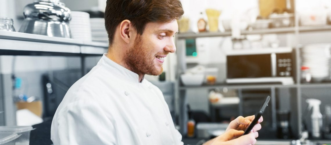cooking, profession and people concept - happy male chef cook with tablet pc computer at restaurant kitchen